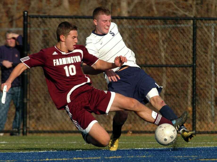 Farmington's #10 Michael DiTomasso rushes in to disrupt a kick to the goal by Staples #9 Brendan Lesch, during the 2010 Boys Soccer State Tournament Class LL final in Waterbury, Conn. on Saturday November 20, 2010. Staples lost to Farmington 2-1. Photo: Christian Abraham / Connecticut Post