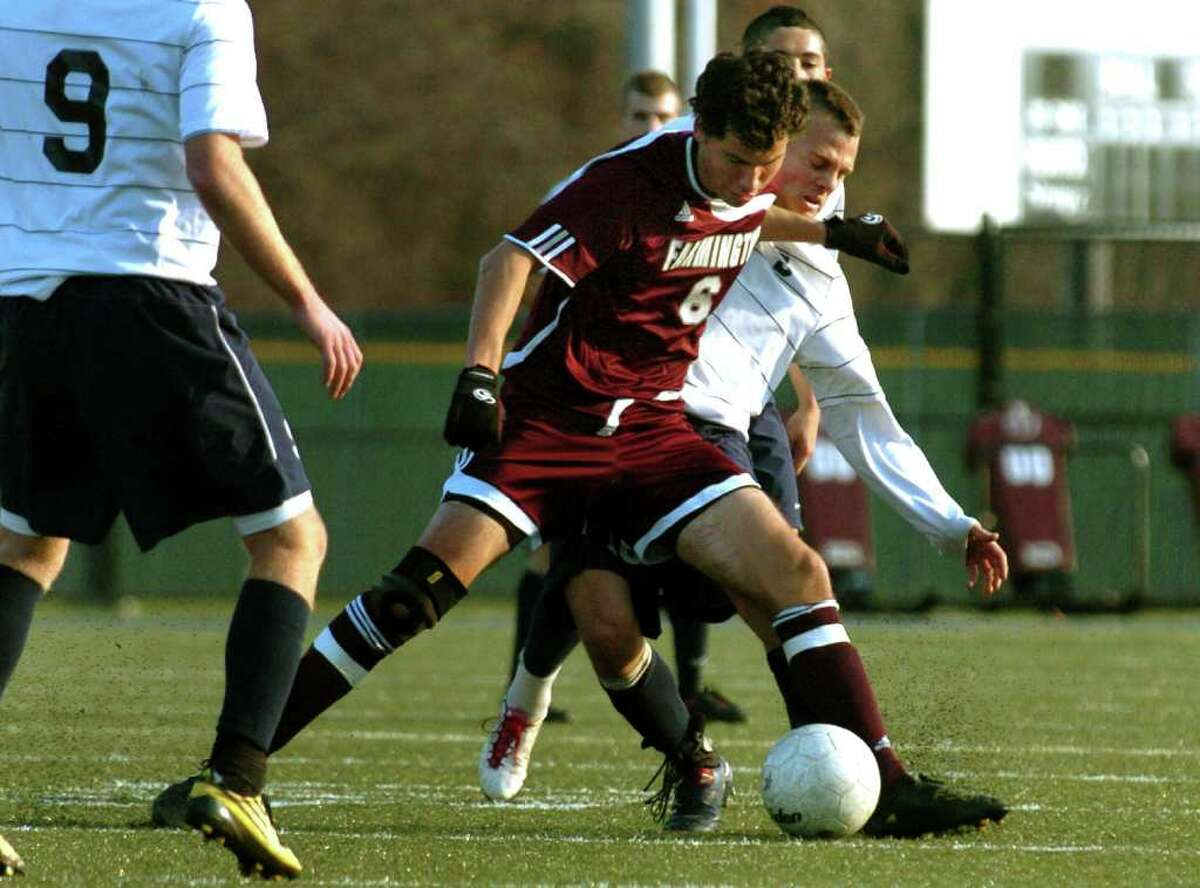 Farmington's #6 Kevin Michalak muscles in on Staples #18 Steven Denowitz, during the 2010 Boys Soccer State Tournament Class LL final in Waterbury, Conn. on Saturday November 20, 2010. Staples lost to Farmington 2-1.