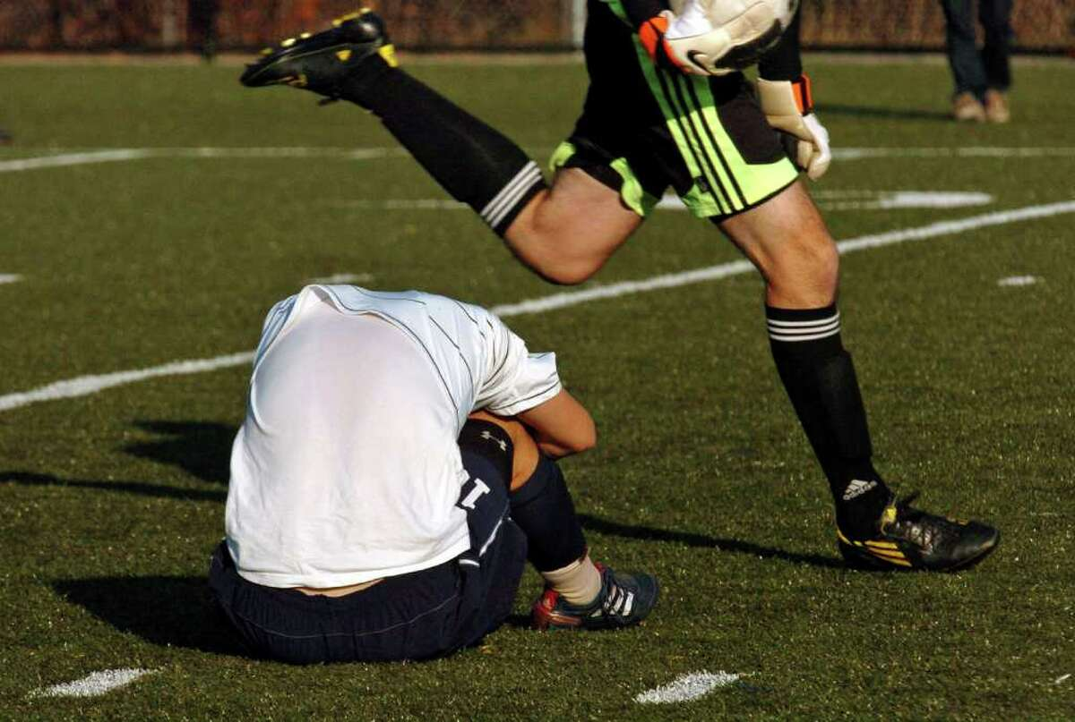 Farmington goalie Austin Peluso runs past as Staples #10 Jacob Krosse buries his head after the team lost 2-1 in the 2010 Boys Soccer State Tournament Class LL final in Waterbury, Conn. on Saturday November 20, 2010.