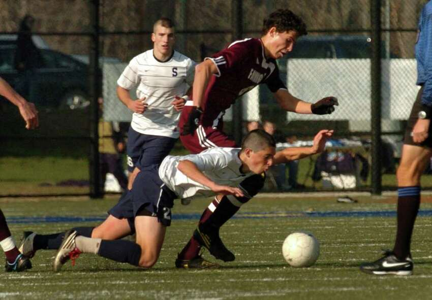 Staples #2 Court Lake takes a spill as he chases down the ball with Farmingham's #6 Kevin Michalak, during the 2010 Boys Soccer State Tournament Class LL final in Waterbury, Conn. on Saturday November 20, 2010. Staples lost to Farmington 2-1.