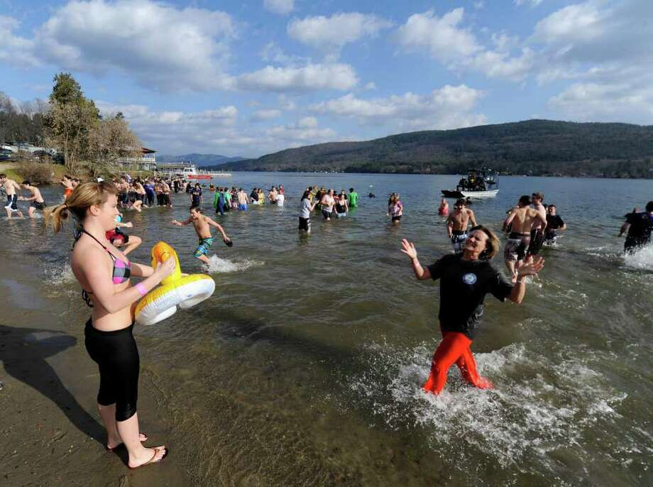 "Barb Johnson Heimroth throws her arms up as she leaves to waters of the lake to visit her daughter, Kelsey, during the ""Polar Bear Plunge"" held Saturday to raise money for Special Olympics in Lake George. (Skip Dickstein/Times Union) Photo: Skip Dickstein / 2008"