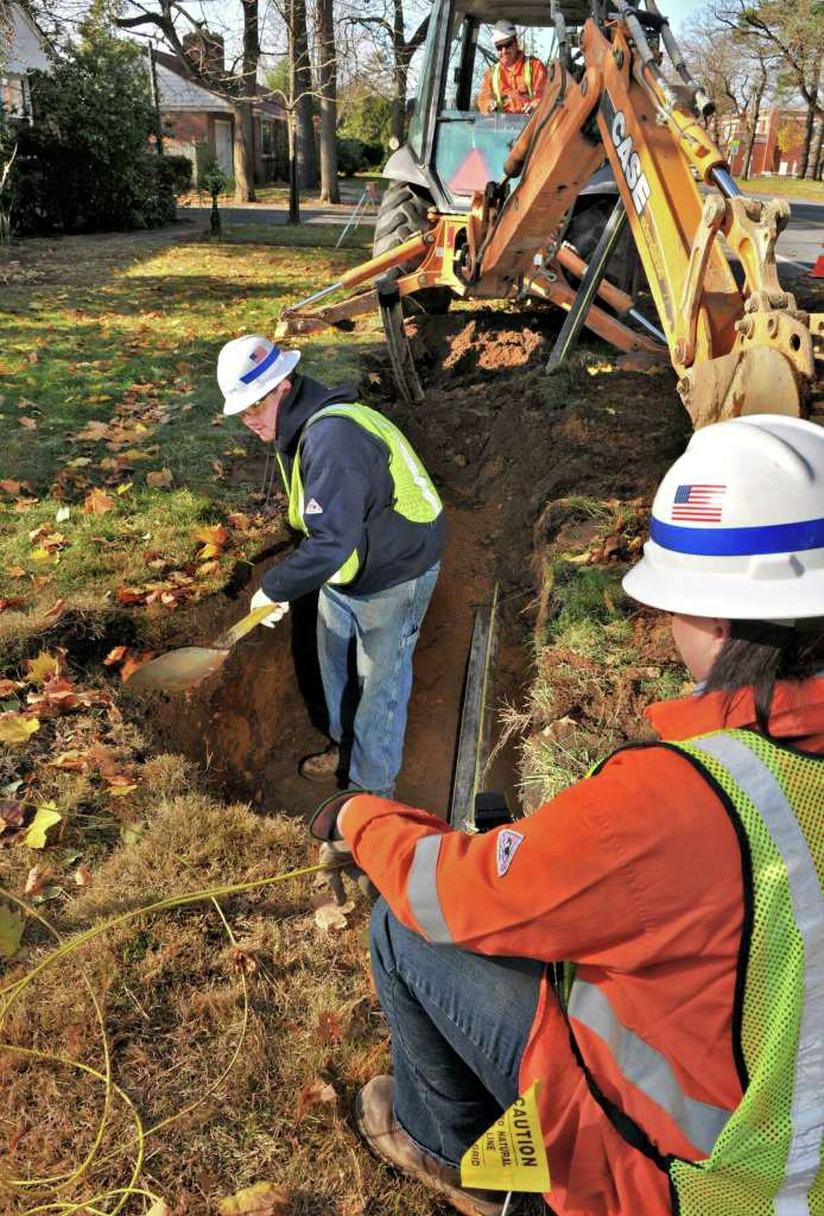 National Grid crew Jason Crowl, left, Tom Bates (in excavator's cab) and Lynn Dunlavey work on a new gas pipe installation on Lake Avenue in Saratoga Springs Thursday morning Nov. 18, 2010. (John Carl D'Annibale / Times Union)