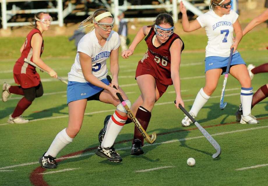 Pomperaug's Abigail Dwyer and Glastonbury's Hayley Hoge vie for the ball as Pomperaug High School shares the state championship with Glastonbury High School for the Class L field hockey state tournament at Wethersfield High School in Wethersfield, CT on Saturday November 20, 2010. Photo: Shelley Cryan / Shelley Cryan freelance; Stamford Advocate Freelance