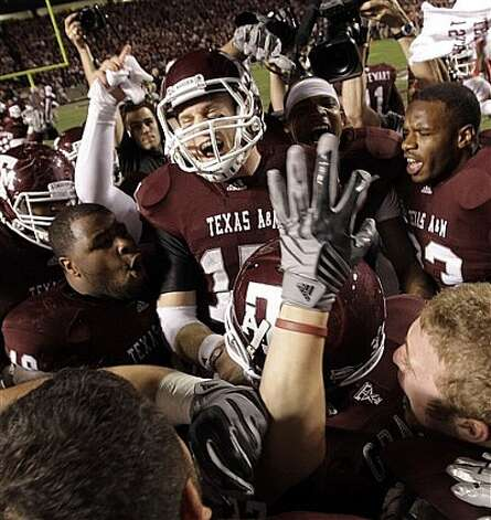 Texas A&M quarterback Ryan Tannehill (center) celebrates with teammates after beating Nebraska.