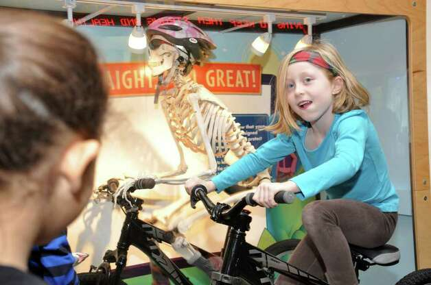 Whitney Scallon, 5, of Darien, operates a bike exhibit which shows how the bones in a skeleton move at Stepping Stones Museum for Children during the grand re-opening on Saturday, Nov. 20, 2010. Photo: Amy Mortensen / Connecticut Post Freelance