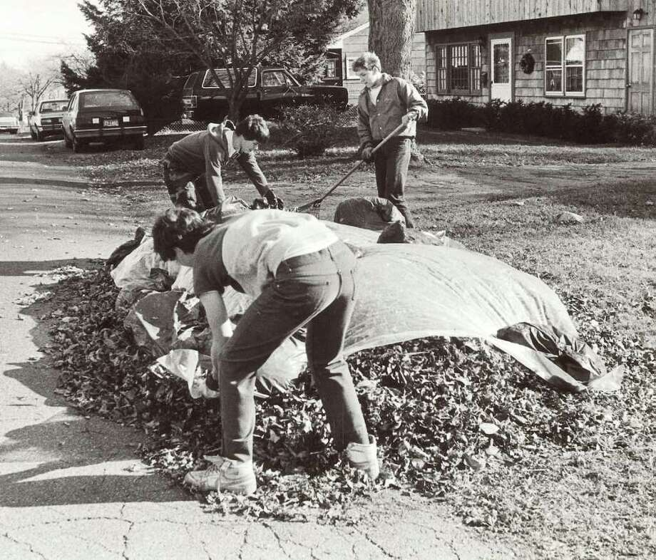 November 24, 1985: Dennis Prindle, 14, of Stamford Catholic High School (foregroud), Ralph Vitti, 14, and Steve Williams, 15, both of Westhill High School, top off a pile of leaves with plastic to keep them from blowing around on Charles St. in the Cove. Photo: Tom Ryan, ST