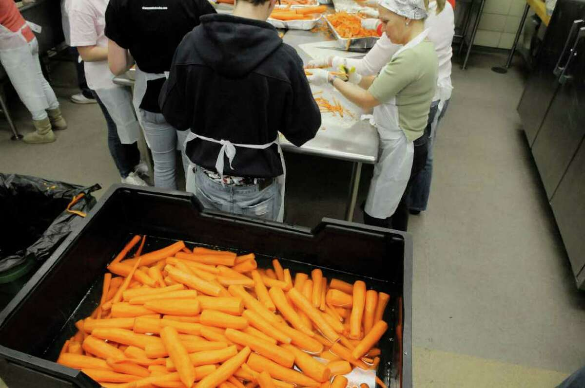 A large bin is filled with peeled carrots as thousands of volunteers turned out at the Empire State Plaza in Albany, on Sunday, Nov. 21. They are preparing meals to be served or delivered to thousands of homeless, homebound and other needy people on Thanksgiving Day.(Paul Buckowski / Times Union)