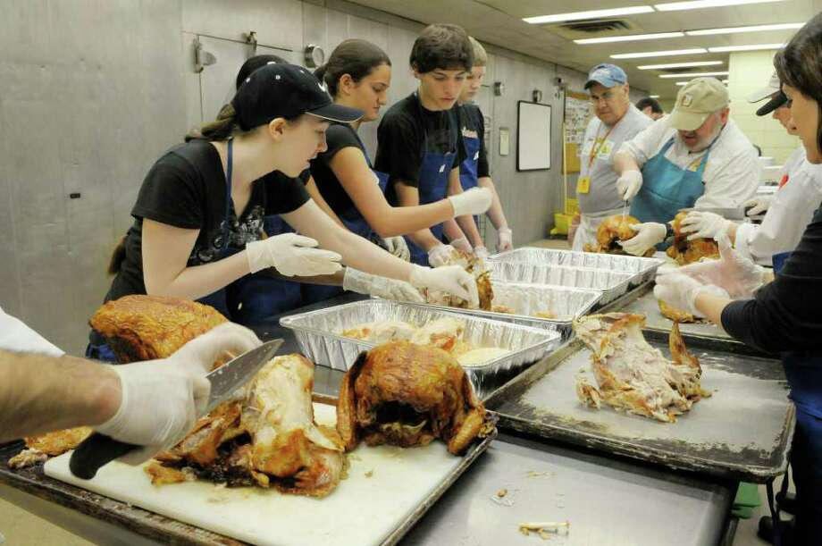 Congregation members from All Saints Catholic Church in Albany work alongside volunteer chefs as they remove turkey meat from the bone. Thousands of volunteers turned out at the Empire State Plaza in Albany on Sunday, Nov. 21, to begin the preparation of making and packaging the meals to be served or delivered to thousands of homeless, homebound or needy people in the Capital Region on Thanksgiving Day.(Paul Buckowski / Times Union) Photo: Paul Buckowski / 00011139A