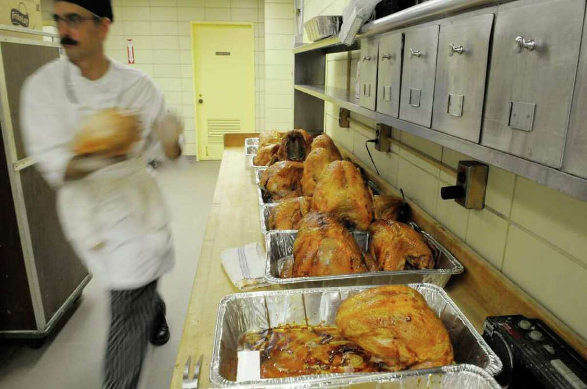 Fresh out of the ovens, turkeys are rushed to the cutting tables where meat will be separated from the bone. They were among thousands of volunteers preparing Thanksgiving Day meals for the needy this holiday .(Paul Buckowski / Times Union)