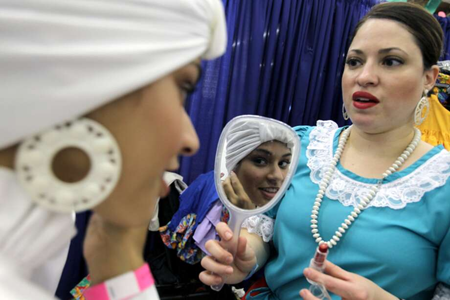 Leslie Ramos (right) holds a hand mirror for Christina Crespo as she dons earrings in preparation for a performance of the Ballet Folklorico Boriken during the 12th biennial Puerto Rican Festival.