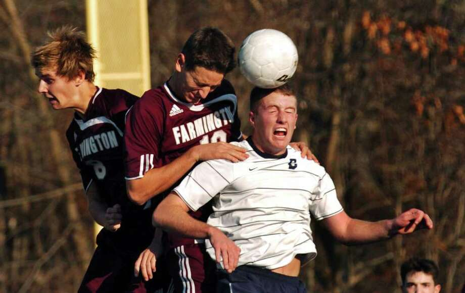 Staples #9 Brendan Lesch, right, tires to head the ball into the net from a sideline kick, during the 2010 Boys Soccer State Tournament Class LL final in Waterbury, Conn. on Saturday November 20, 2010. At left is Farmington's #8 Colin Troxell and his teammate #10 Michael DiTomasso. Staples was defeated 2-1. Photo: Christian Abraham / Connecticut Post