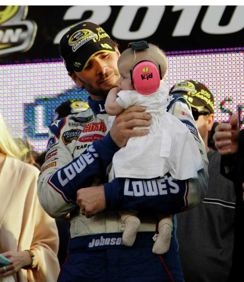 NASCAR driver Jimmie Johnson holds his daugher, Geneviene, after winning his fifth Sprint Cup Series Championship Sunday, Nov. 21, 2010 in Homestead, Fla.(AP Photo/Terry Renna) Photo: AP