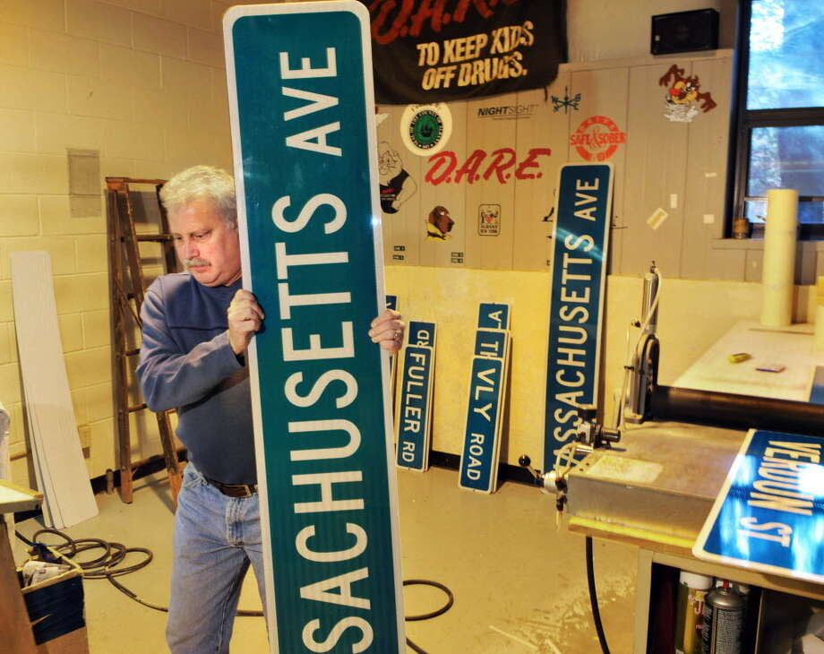 Sign technician Tom Phelan with new street signs in the sign shop at the Colonie Public Operation Center. (John Carl D'Annibale / Times Union)