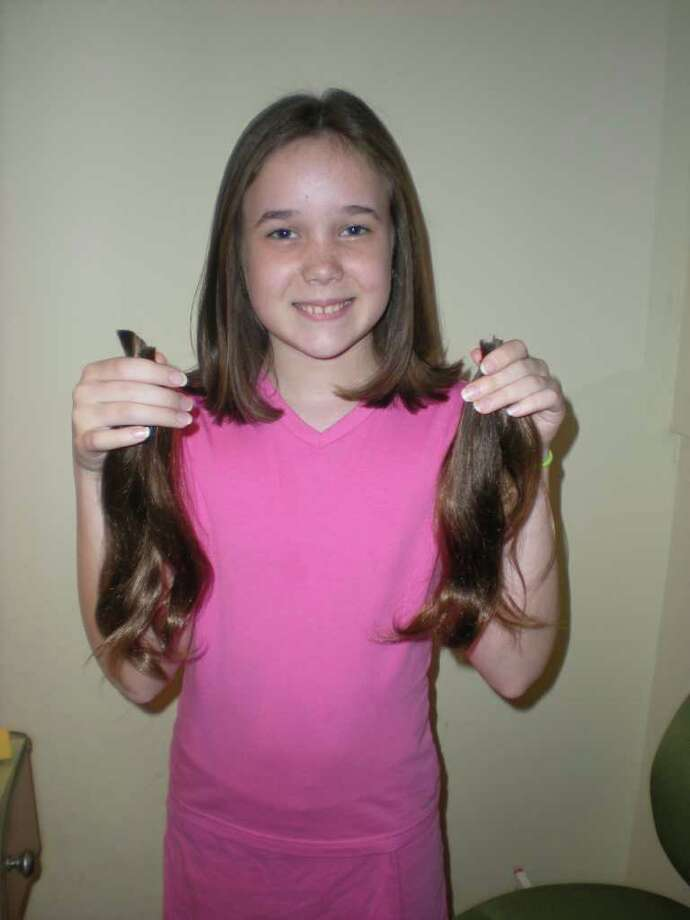 Westport's Katie Simpson, an 11-year-old sixth grader at Bedford Middle School, holds the hair she cut on Monday, Nov. 22, 2010, to donate it to Locks of Love. Photo: Contributed Photo / Westport News contributed
