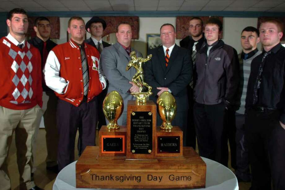 Members of the Derby High School football team (left), and the Shelton High School football team (right) stand behind the Derby-Shelton Rotary Club Thanksgiving Day Trophy in Shelton, Conn. Nov. 23rd, 2010. This year's game will be the 100th time that the teams have played each other. Seen from left are Derby senior captains Jonathan Haydu, Zach Salazar, Jesse Gilbert and Richard Bartone with coach George French. Sheton coach Jeff Roy stands with his senior captains, from left, Mike Georgalas, Jon Groth, Cody Kitson and Ryan DeAngelis. Photo: Ned Gerard / Connecticut Post