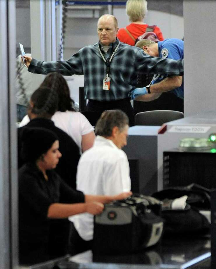 An traveller is patted down by a TSA agent at O'Hare International Airport in Chicago, Monday, Nov. 22, 2010. There are new requirements at some U.S. airports that air passengers must pass through full-body scanners that produce a virtually naked image. Those who refuse to go through the scanners are subject to thorough pat-downs. (AP Photo/Paul Beaty) Photo: Paul Beaty, FRE / FR36811 AP