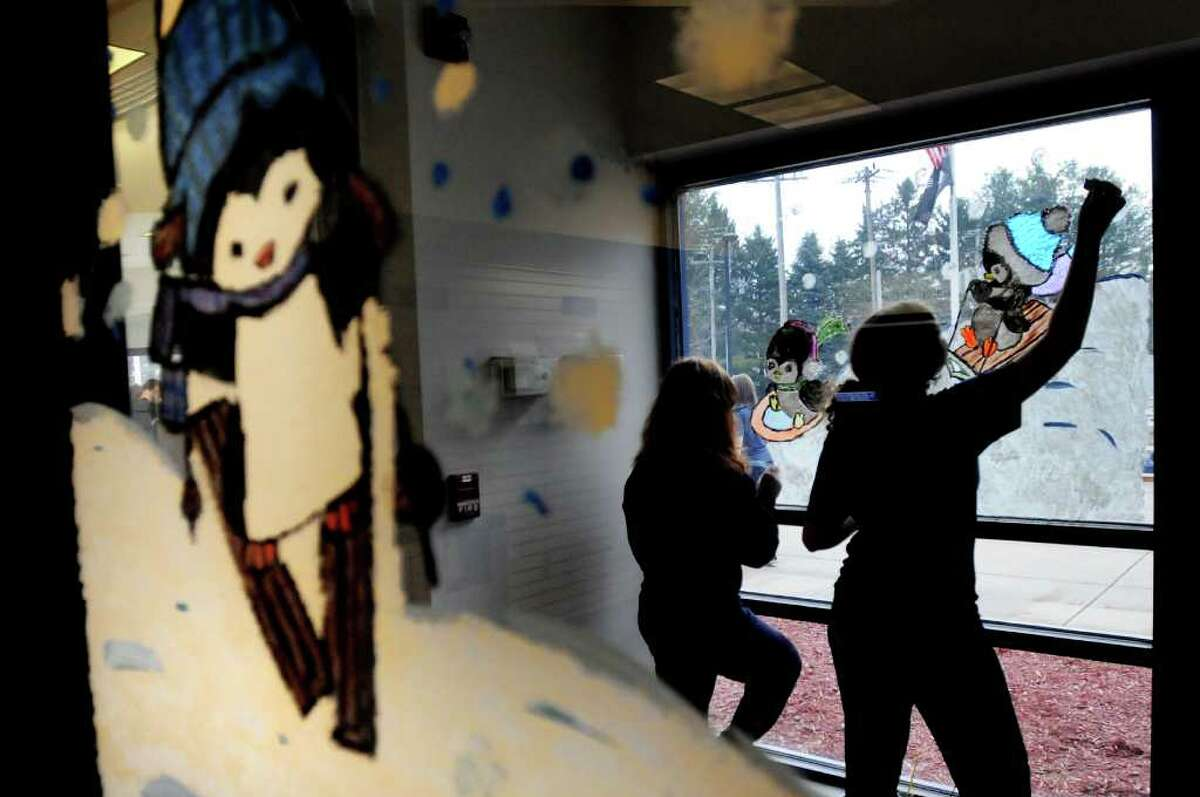 St. Ambrose School eighth-graders Danielle Zaccaria, 13, left, and Shannon Donovan, 13, paint a holiday scene in the entryway on Tuesday, Nov. 23, 2010, at the Main Post Office in Latham, N.Y. This is the 11th year that the students have painted the windows. (Cindy Schultz / Times Union)