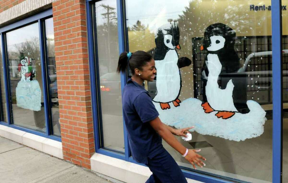 St. Ambrose School eighth-grader Kyaira Coffin, 13, delights at the final result when she sees her holiday-scene painting from the outside on Tuesday, Nov. 23, 2010, at the Main Post Office in Latham, N.Y. This is the 11th year that the students have painted the windows. (Cindy Schultz / Times Union)