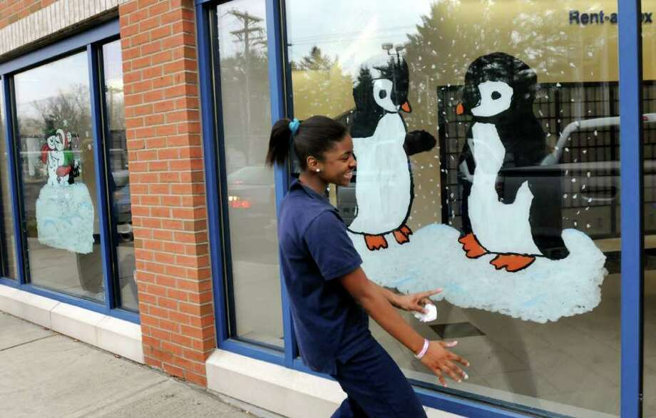 St. Ambrose School eighth-grader Kyaira Coffin, 13, delights at the final result when she sees her holiday-scene painting from the outside on Tuesday, Nov. 23, 2010, at the Main Post Office in Latham, N.Y. This is the 11th year that the students have painted the windows. (Cindy Schultz / Times Union) Photo: Cindy Schultz