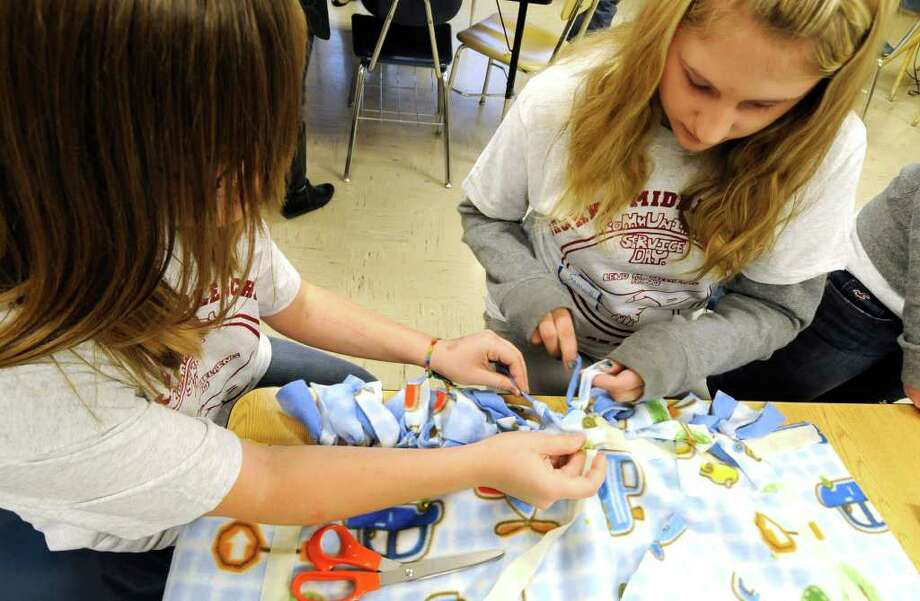 Eighth-grade students Samantha Wessell, left, and Victoria Peters of the O'Rourke Middle School in Burnt Hills work on no-sew blankets to be distributed to The Children's Hospital at Albany Medical Center Hospital on the occasion of Service Day at the school November 23, 2010. (Skip Dickstein/Times Union) Photo: Skip Dickstein / 2008