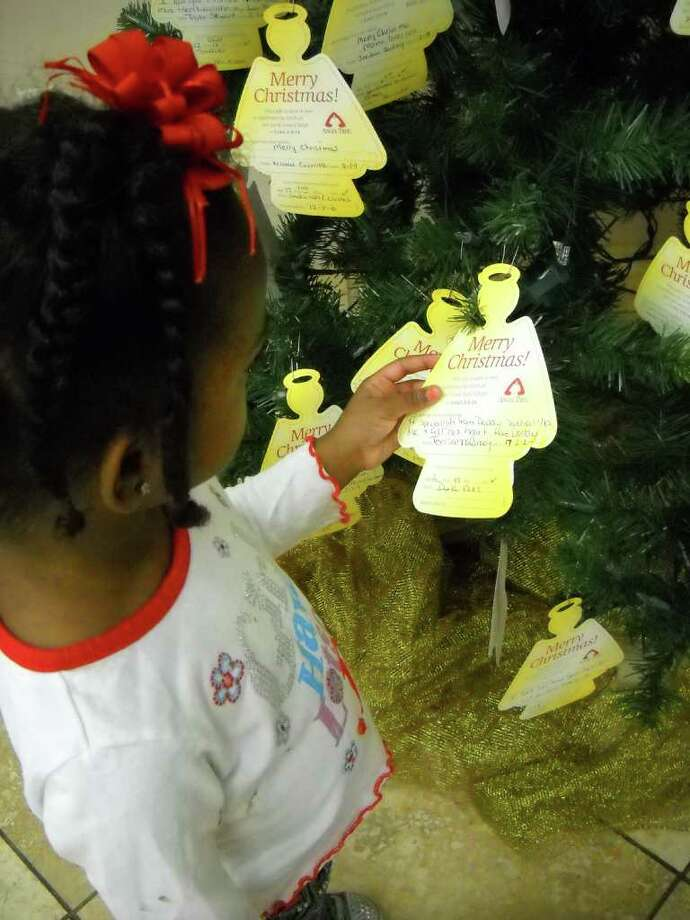 Two-year-old M'Kayla Walker picks a name from the Angel Tree at Triumph Church in Beaumont. The church is sponsoring the Angel Tree as part of a program that allows children with incarcerated parents to receive Christmas gifts. Heather Nolan/The Enterprise