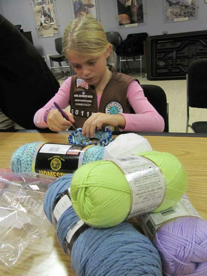"Hannah Paprotna, a member of Brownie Troop 50115, makes a cap for an infant child in a developing country. The effort is part of Save the Children's ""Caps For Good"" campaign. Photo: Contributed Photo / Westport News"