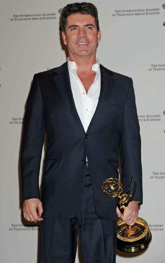 Simon Cowell poses with his award at the 38th International Emmy Awards, Monday, Nov. 22, 2010, in New York. (AP Photo/Louis Lanzano) Photo: Louis Lanzano