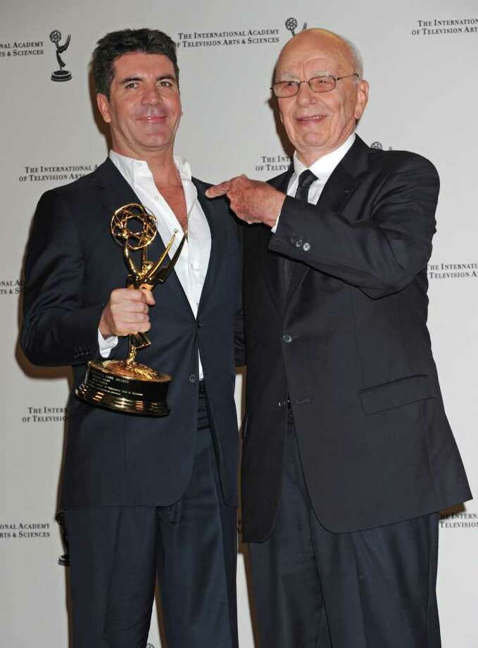 Simon Cowell poses after receiving his award with media magnate Rupert Murdock  at the 38th  International Emmy Awards, Monday, Nov. 22, 2010, in New York. (AP Photo/ Louis Lanzano) Photo: Louis Lanzano