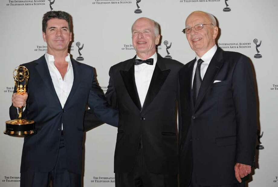 Award recipient Simon Cowell poses with Bruce Paysner, center, President and CEO of the International Academy of Television Arts and Sciences and media magnate Rupert Murdock at the 38th  International Emmy Awards, Monday, Nov. 22, 2010, in New York. (AP Photo/Louis Lanzano) Photo: Louis Lanzano