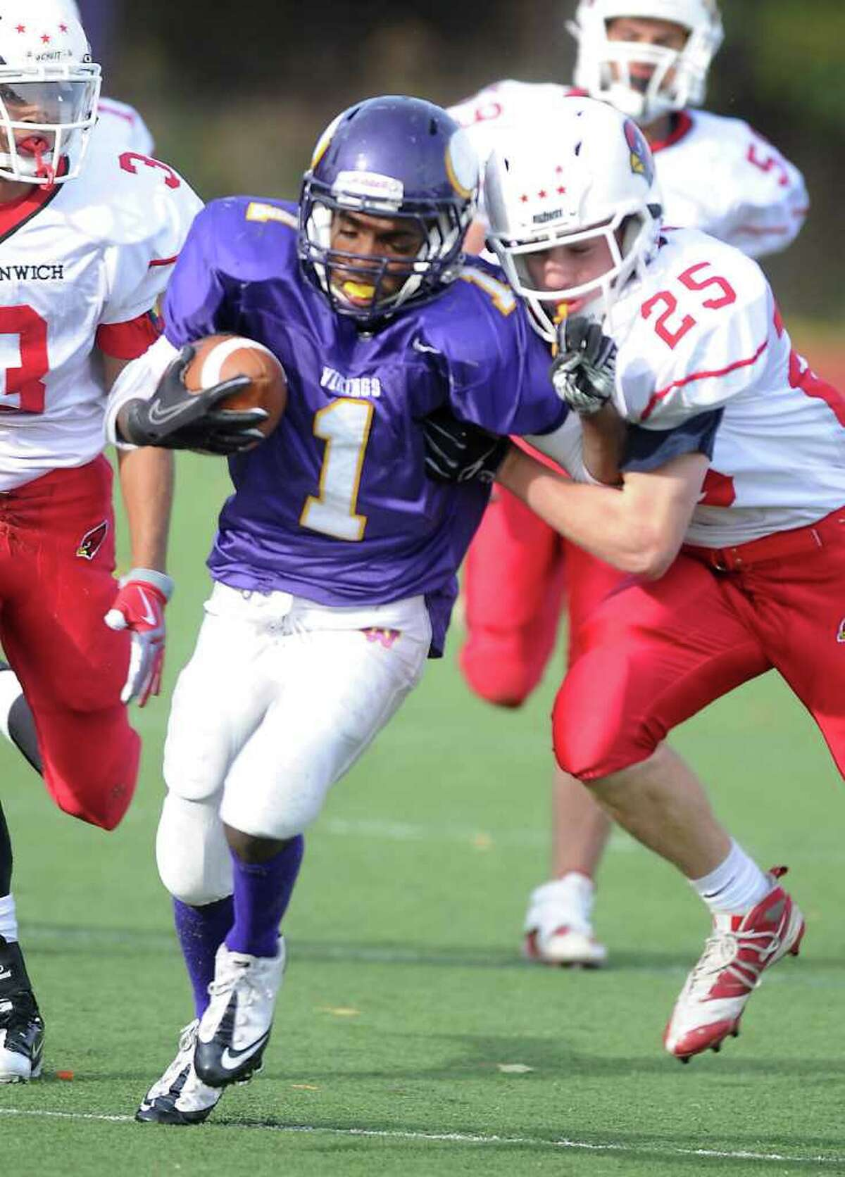 Westhill High School's Akai Jackson os stopped by Greenwich High School's Ryan Kelly in football action in Stamford, Conn. on Saturday October 30, 2010.