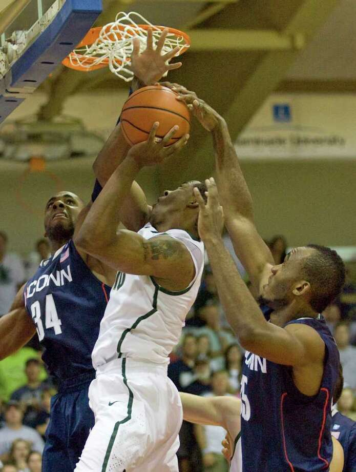 Connecticut's Alex Oriakhi (34) and Charles Okwandu, right, battle Michigan State  forward Delvon Roe, center, for the basketball in the first half of a NCAA college basketball game at the Maui Invitational in Lahaina, Hawaii Tuesday, Nov. 23, 2010. (AP Photo/Eugene Tanner) Photo: AP