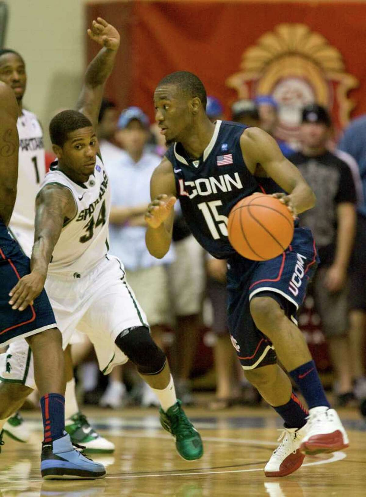 Michigan State guard Korie Lucious (34) attempts to defend Connecticut guard Kemba Walker (15) in the second half of an NCAA college basketball game at the Maui Invitational in Lahaina, Hawaii Tuesday, Nov. 23, 2010. Connecticut defeated Michigan State 70-67 to advance to the championship game. (AP Photo/Eugene Tanner)