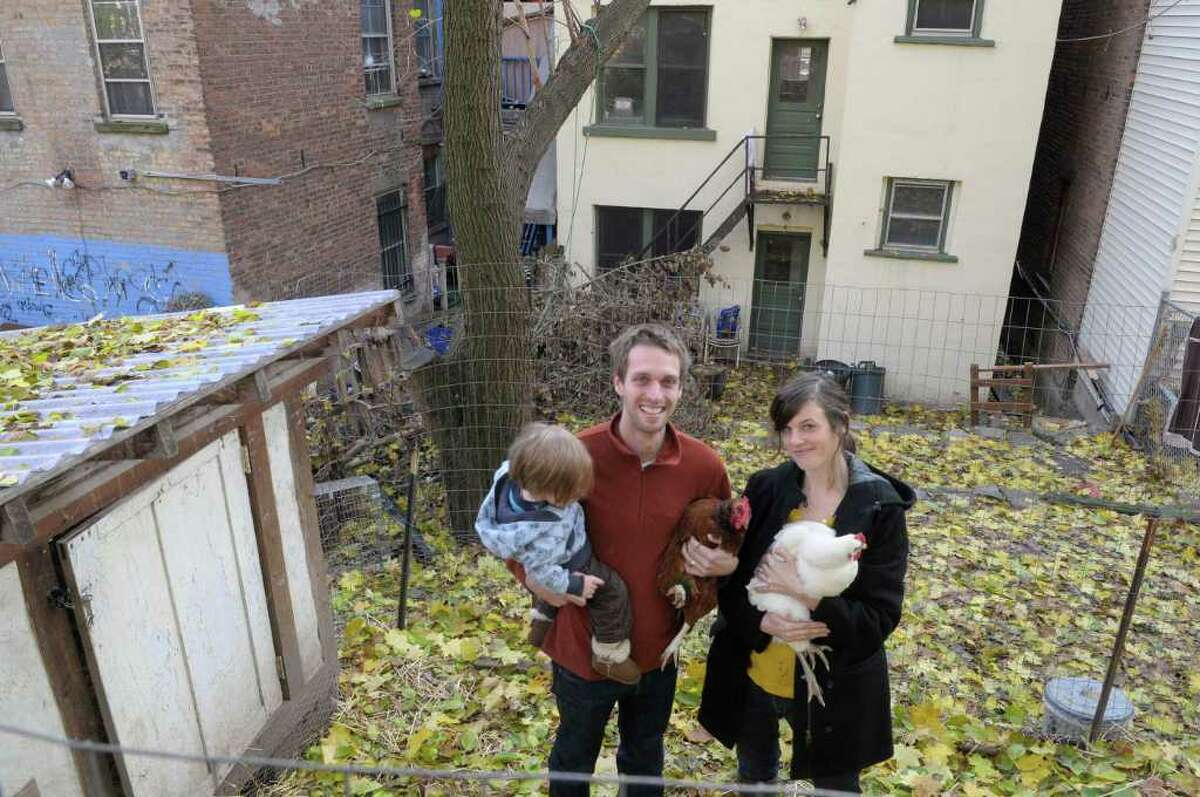 Mike Guidice, his wife Jen Pursley, and their child Thatcher Guidice, 15 months old, pose with some of their chickens in the pen where the chickens use to live in the backyard of their Albany home. The city ordered them to get rid of their chickens in accordance with city code, which bans farm life and fowl. (Paul Buckowski / Times Union)