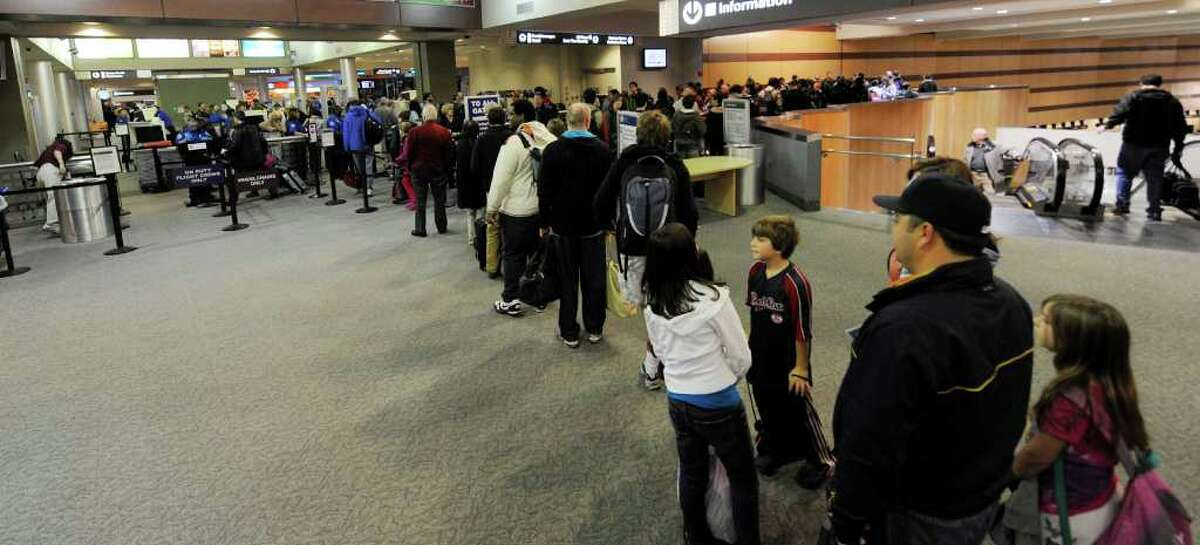 Travelers wait at the security checkpoint during Wednesday's busy pre-Thanksgiving travel crush at Albany International Airport. (SKIP DICKSTEIN / TIMES UNION)