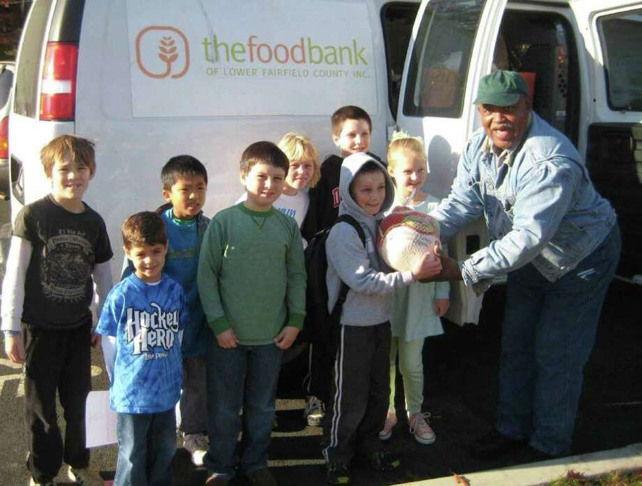 Pictured handing the turkeys to the food bank are, from left, Callum McNear, Ian McCarthy, Edward Chin, Reilly Buckley, Brianna Lyons, Mac Mclaughlin, Ben Hathaway and Kerry McDermott. Photo: Contributed Photo / Darien News