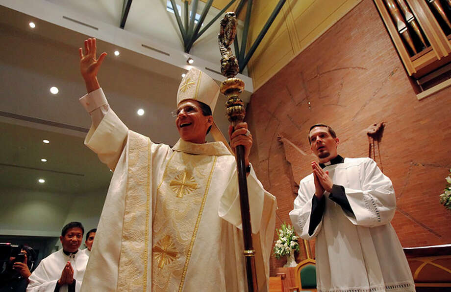 Archbishop Gustavo Garica-Siller (center) waves to his parishioners at the conclusion of the installation service at St. Mark The Evangelist Church on Nov. 23. (Photo by Kin Man Hui/Express-News)
