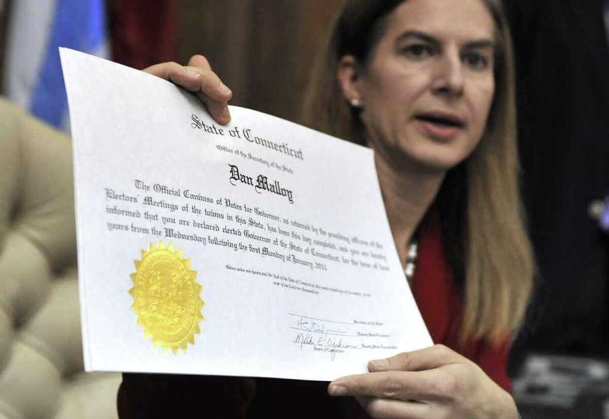 Connecticut Secretary of the State Susan Bysiewicz holds up a certificate she will sign certifying the Nov. 2 election for Governor-elect Dan Malloy her office at the Capitol in Hartford, Conn., Wednesday, Nov. 24, 2010. (AP Photo/Jessica Hill)