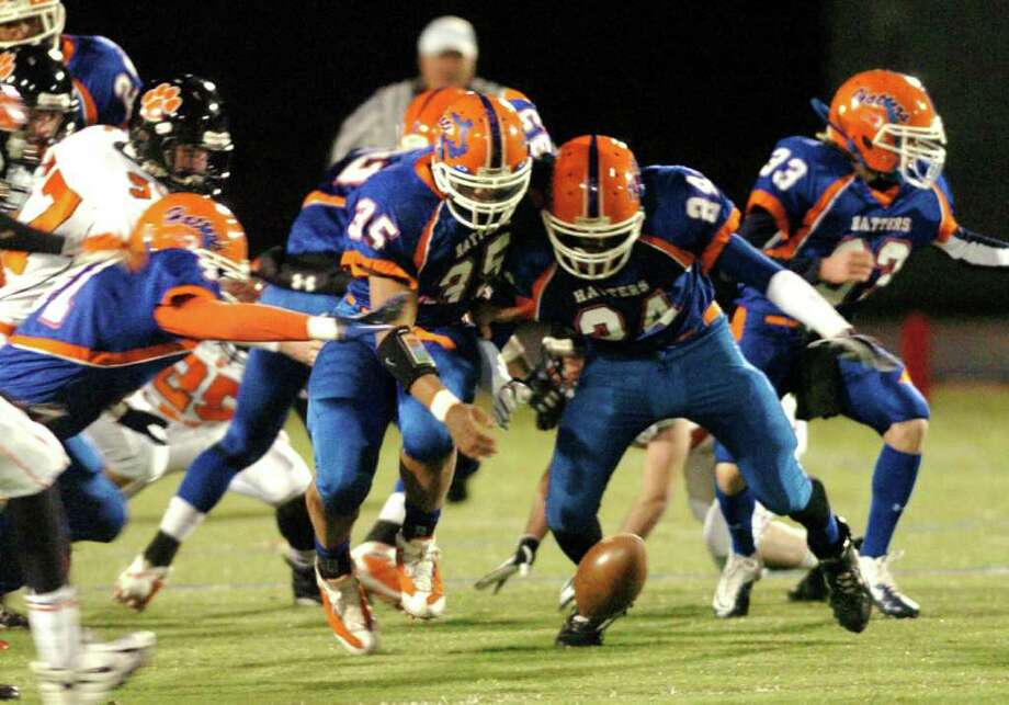 Danbury's 24, Trevon Dickens and 35, Austin Calitro fumble over the ball during the football game against Ridgefield at Danbury High School Nov. 24, 2010. Photo: Chris Ware / The News-Times