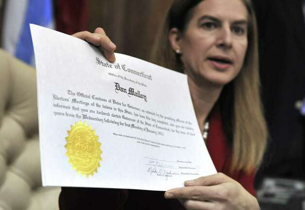 Connecticut Secretary of the State Susan Bysiewicz holds up a certificate she will sign certifying the Nov. 2 election for Governor-elect Dan Malloy her office at the Capitol in Hartford, Conn., Wednesday, Nov. 24, 2010.  (AP Photo/Jessica Hill) Photo: Jessica Hill, AP / AP2010