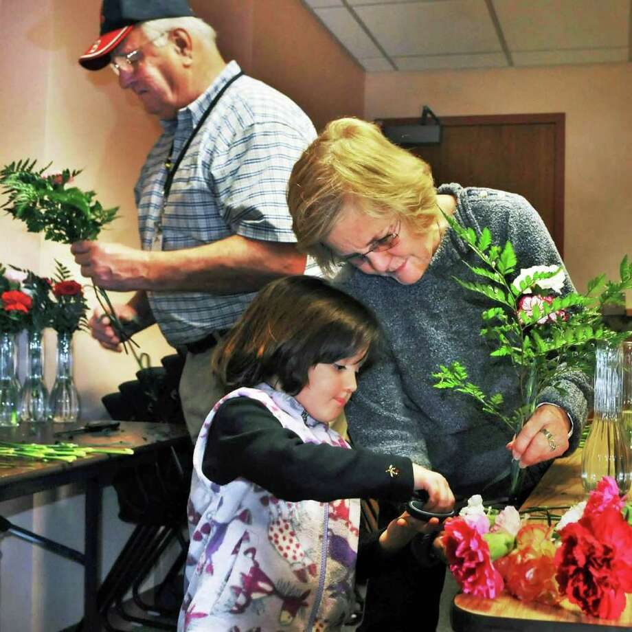 4-year-old Natasha Hurff helps her grandmother Anne Hunscher and other volunteers making flower arrangements to for patients and residents who spend Thanksgiving in Saratoga Hospital and Saratoga Care Nursing Home, courtesy of The Saratoga Hospital Volunteer Guild at Saratoga Hospital Wednesday afternoon. At left is Joe Regan.   (John Carl D'Annibale / Times Union) Photo: John Carl D'Annibale / 00011194A