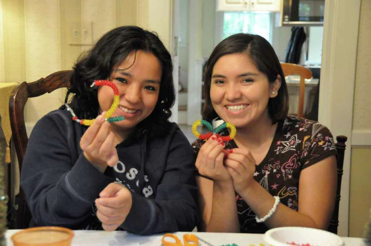 Claudia Ramirez and Claudia Zenteno, both from Bolivia, make Christmas ornaments in the colors of the Bolivian flag for The Festival of Trees, the principal annual fundraiser of the Junior League of Greenwich.