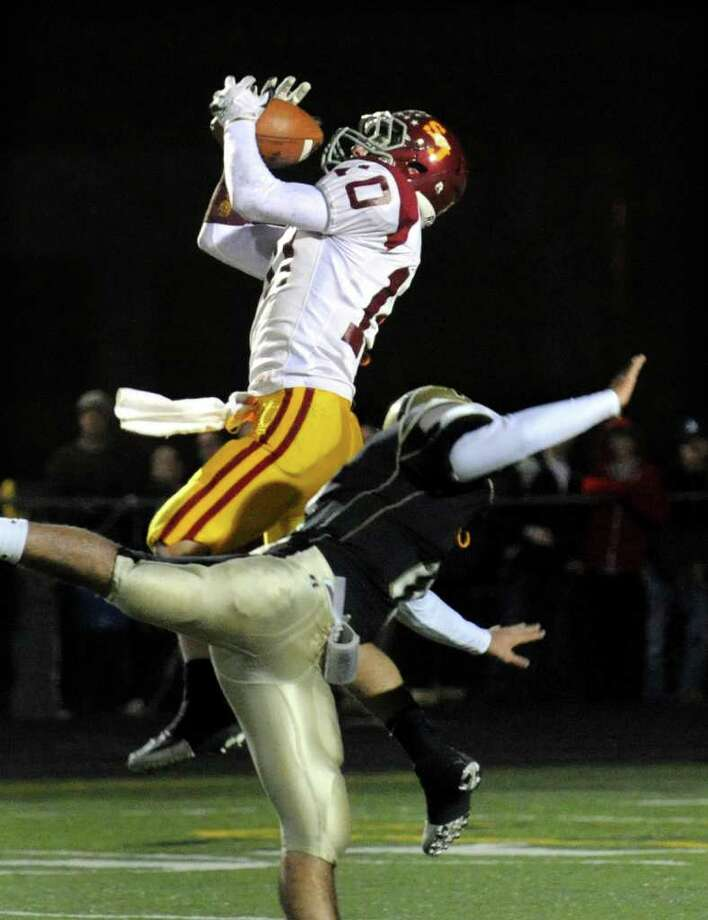 St. Joseph's #10 Pat Mulligan catches a pass mid-air as Trumbull's #11 Anthony Matera falls along side, during football action in Trumbull, Conn. on Wednesday November 24, 2010. Photo: Christian Abraham / Connecticut Post