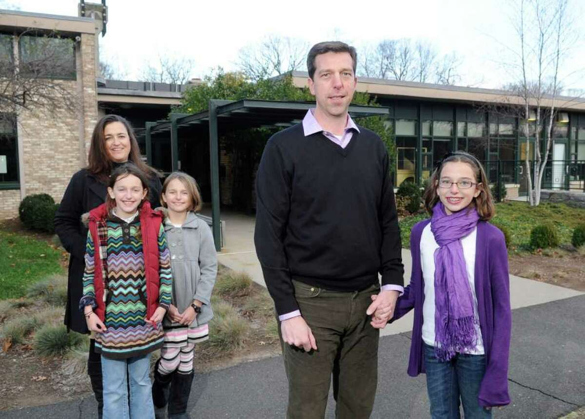 John and Laura Kavounas, husband and wife, posed with their children in front of The Whitby School, Greenwich, Wednesday, Nov. 24, 2010. Laura is shown with twins Annie, left and Katie, both 9 and fourth-graders at the school and John is shown with Lizzie, 11, a fifth-grader at the school.
