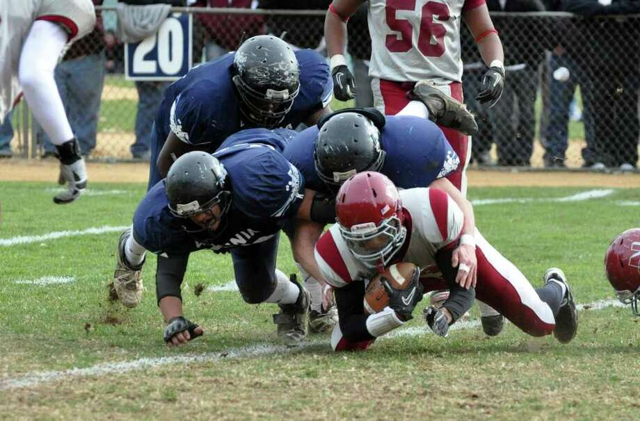 Naugatuck's Rueban Berger is tackled by a host of Ansonia defensemen during the Thanksgiving day football game at Jarvis Field at the Nolan Athletic Complex in Ansonia on Thursday, Nov. 25, 2010. Photo: Amy Mortensen / Connecticut Post Freelance