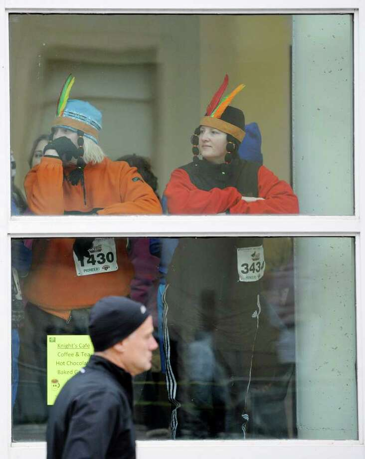 Two Turkey Trotters stay warm in the Troy Atrium before the annual Turkey Trot race in Troy. (SKIP DICKSTEIN / TIMES UNION) Photo: Skip Dickstein