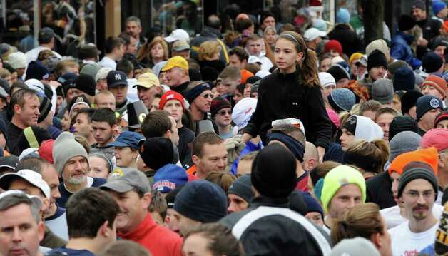 A young woman has a good seat before the annual Turkey Trot race in Troy November 25, 2010. (SKIP DICKSTEIN / TIMES UNION) Photo: Skip Dickstein