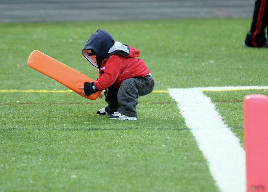 Thanksgiving Day Classic football action highlights between Shelton and Derby in Shelton, Conn. on Thursday November 24, 2010. Luke Solsbury, 14 months, plays with the endzone marker. Photo: Christian Abraham / Connecticut Post