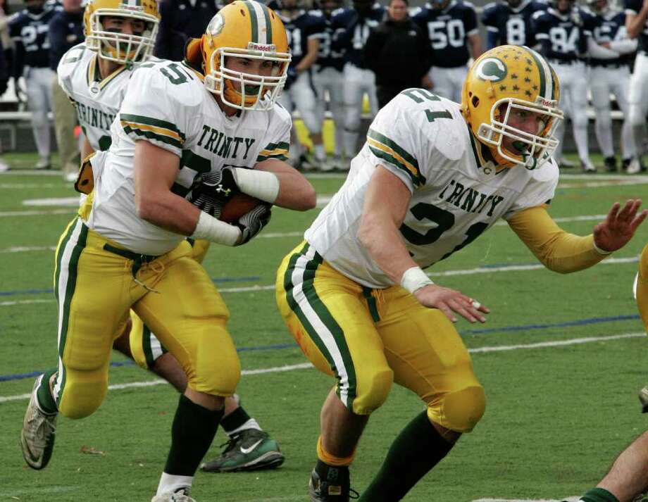Trinity Catholic running back Jeff Cortese, left, gets some blocking help from team captain Mike Rivas during Thursday mornings game against Wilton. Photo: David Ames / Stamford Advocate