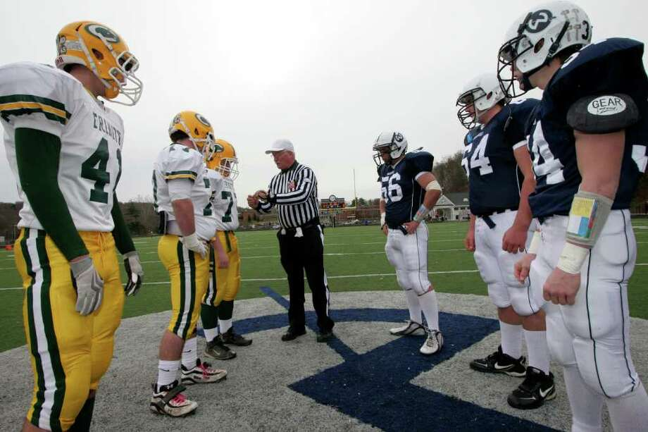 Players from Trinity Catholic High School and Wilton High School wait for the coin toss before Thursday mornings game in Wilton. Photo: David Ames / Stamford Advocate