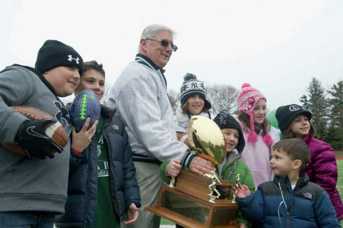 Norwalk Coach Pete Tucci and his grandchildren pose with the Sam Testa Trophy Thanksgiving Day, November 25, 2010. The Bears beat McMahon in a crosstown bout 8-7 in what was Tucci's final game.
